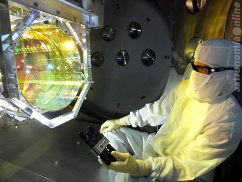 Antes de sellar la cámara y encender las bombas de vacío, un técnico inspecciona una de las ópticas principales del detector LIGO, un espejo, iluminando su superficie a un cierto ángulo. Es fundamental que no haya contaminación en ninguna de las superficies ópticas del instrumento para la operación de LIGO. Créditos de la imagen: LIGO / Caltech / MIT.